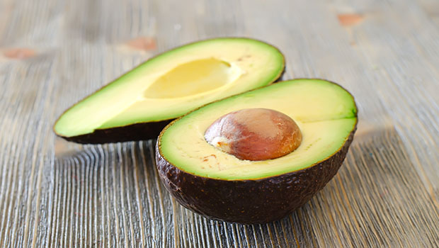 Avocado cut in halves with stone on wooden table